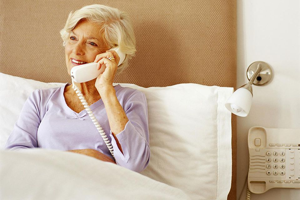 Senior woman sitting in bed, using telephone