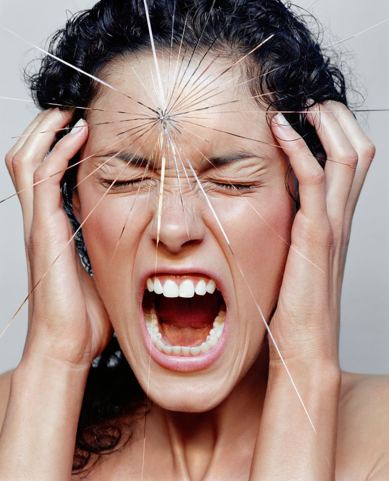 Young woman screaming behind cracked glass