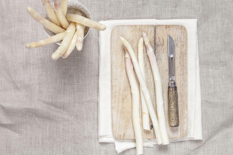 White asparagus, chopping board and peeler