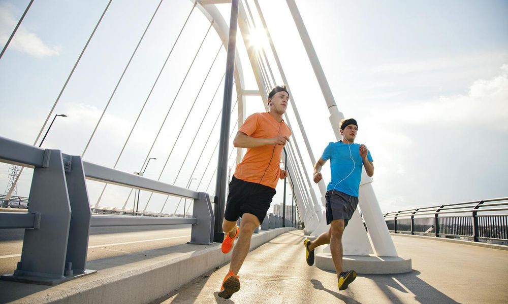 Two young guys stretching, running and working out together outside in a urban area on a sunny day.