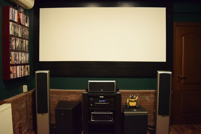 A home stereo system set up in the corner of a room, in front of a screen