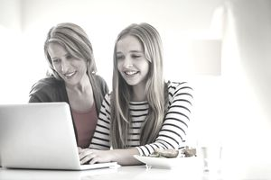 Mother and daughter using laptop together at home