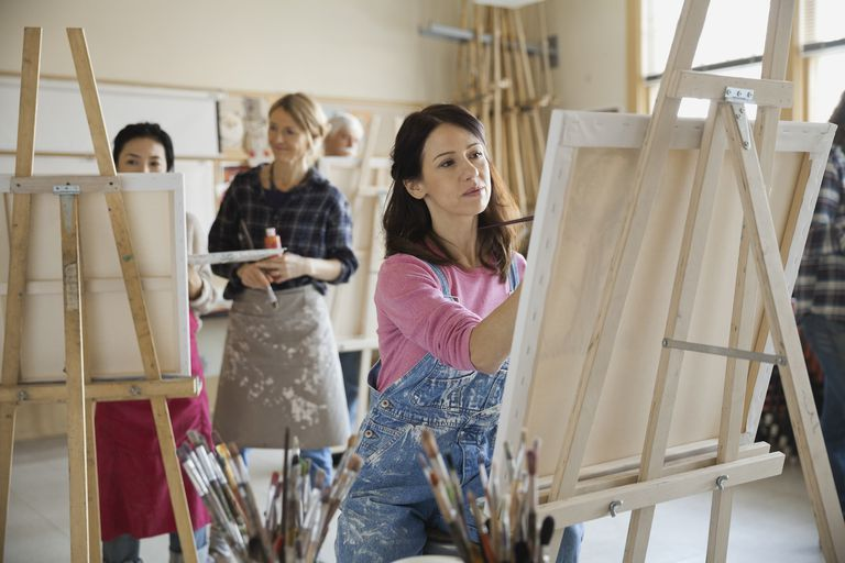 Beautiful woman painting on canvas in art studio