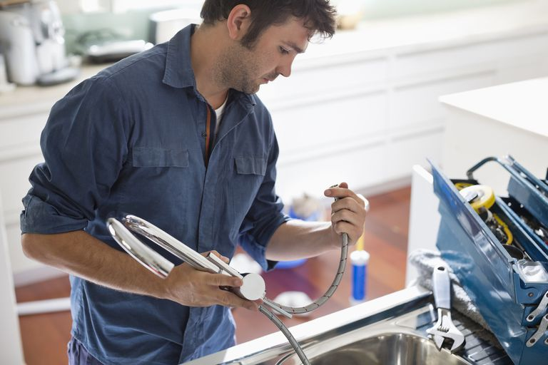 plumber working on kitchen sink paul bradburygetty images