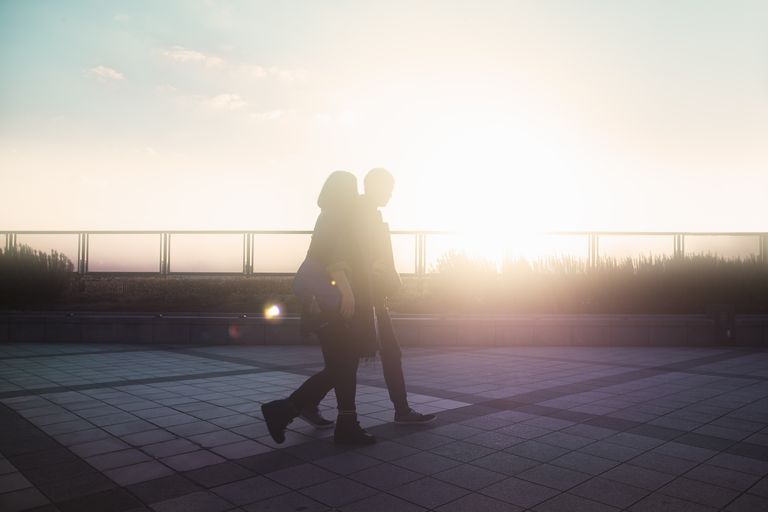 Couple walking on the pavement at sunset, trying to relax during stressful fertility treatments