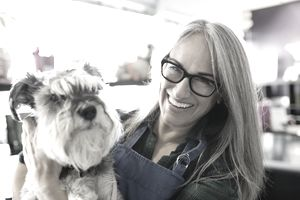 Portrait of smiling dog daycare owner with schnauzer.