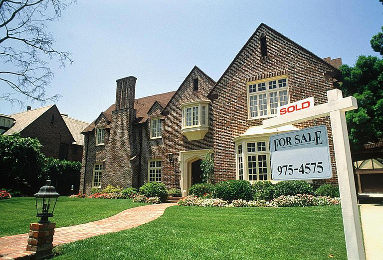 Two-storey brick house with 'sold' sign on lawn