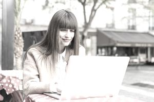 Young woman using laptop in pavement cafe