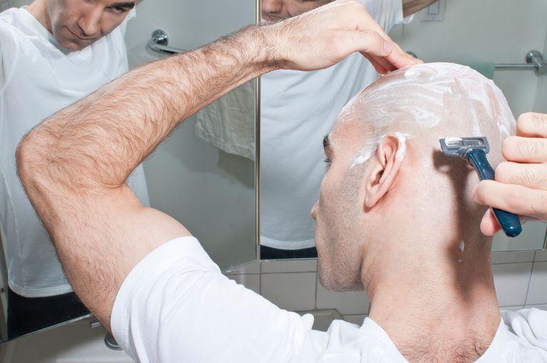 man shaving his head bald
