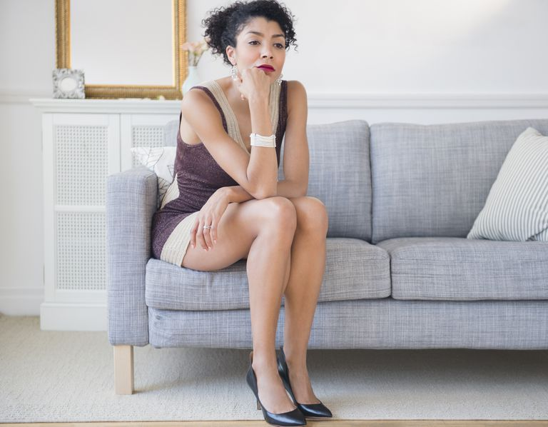 Mixed race woman in cocktail dress sitting on sofa