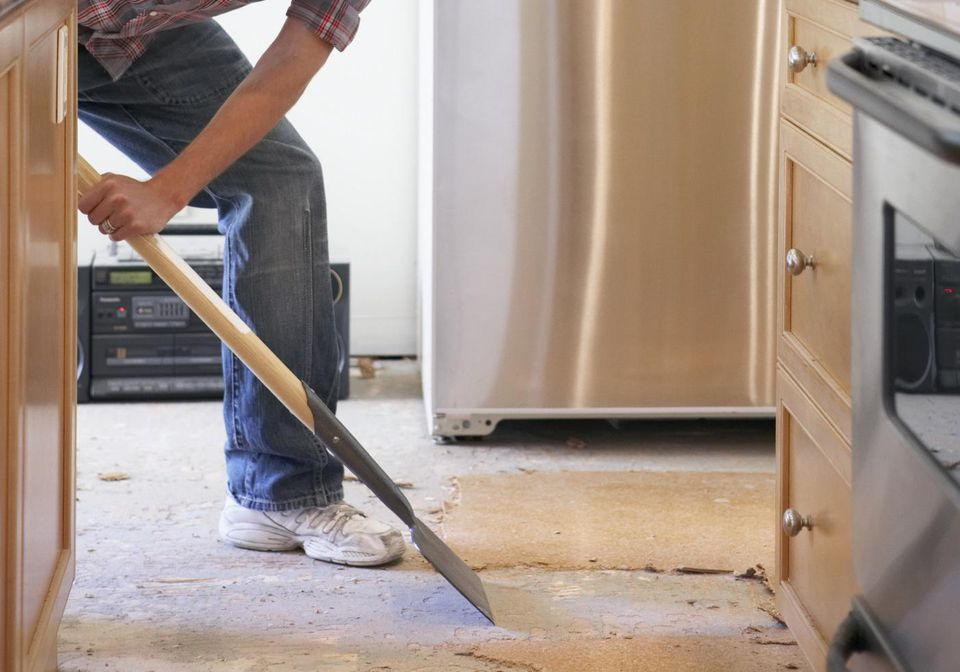 Young man removing flooring in domestic kitchen, side view