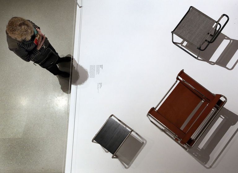 Overhead view of three Marcel Breuer tubular chairs on exhibit with visitor looking on