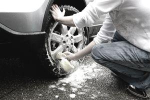 Kid washing wheel of a car