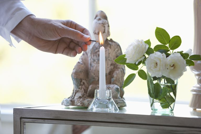 Man Lighting Candle on Altar