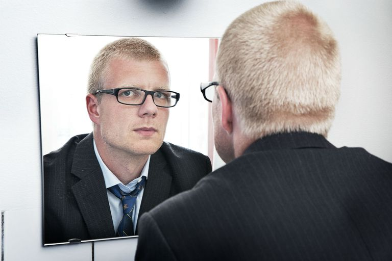 Man with glasses staring at himself in the mirror