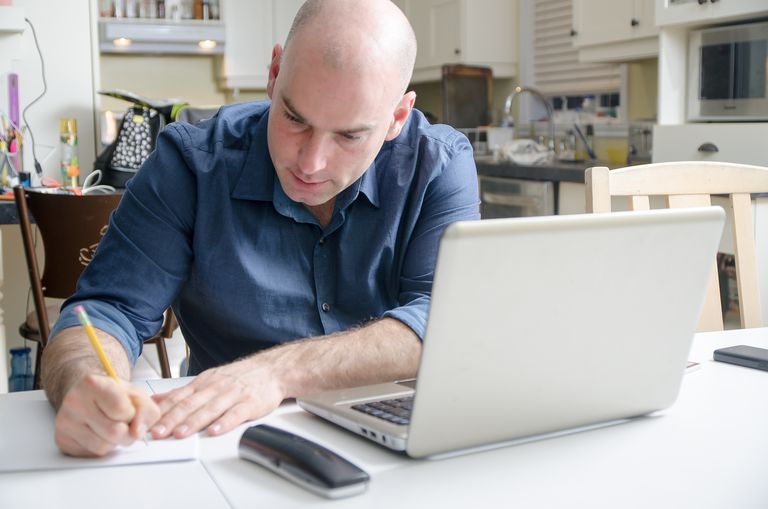 man writing in front of laptop