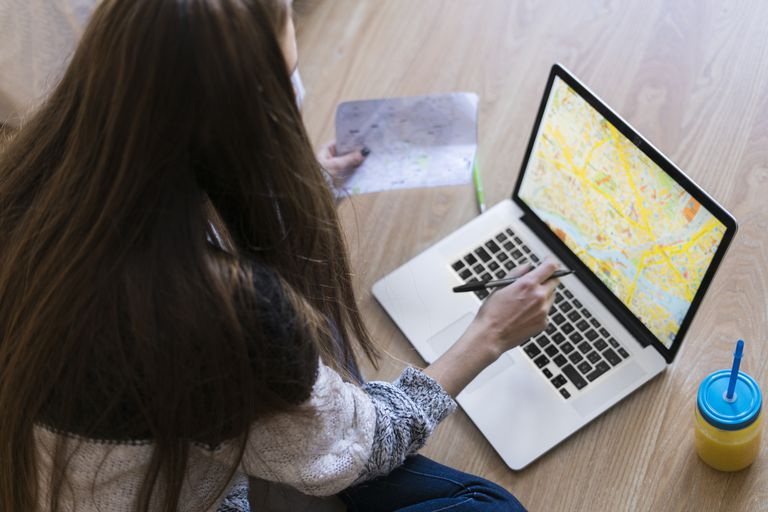 Young woman sitting on the floor looking at map on laptop