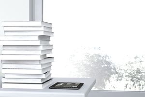 Stack of books next to ereader