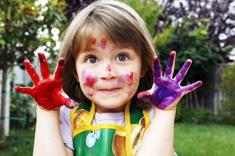 Young girl with paint all over her face and hands
