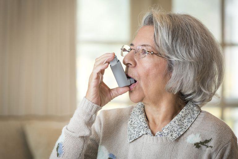 Close up of older Hispanic woman using asthma inhaler
