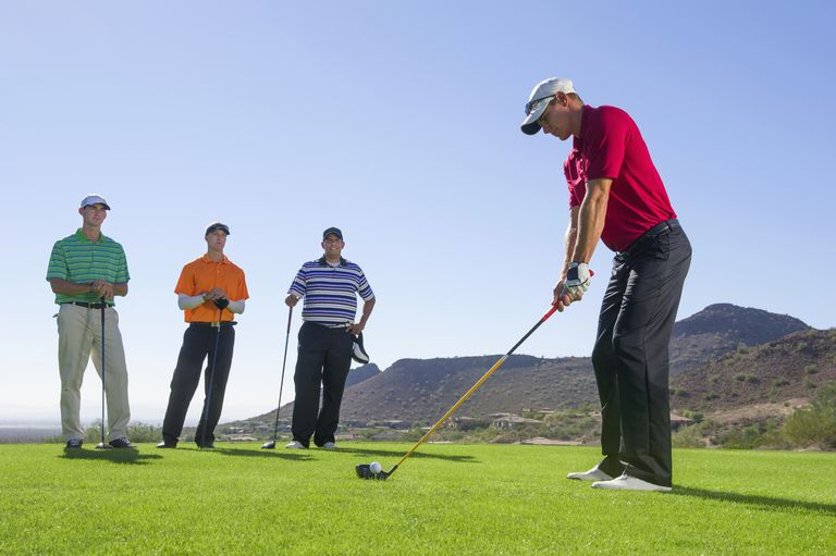 Men playing golf on course.