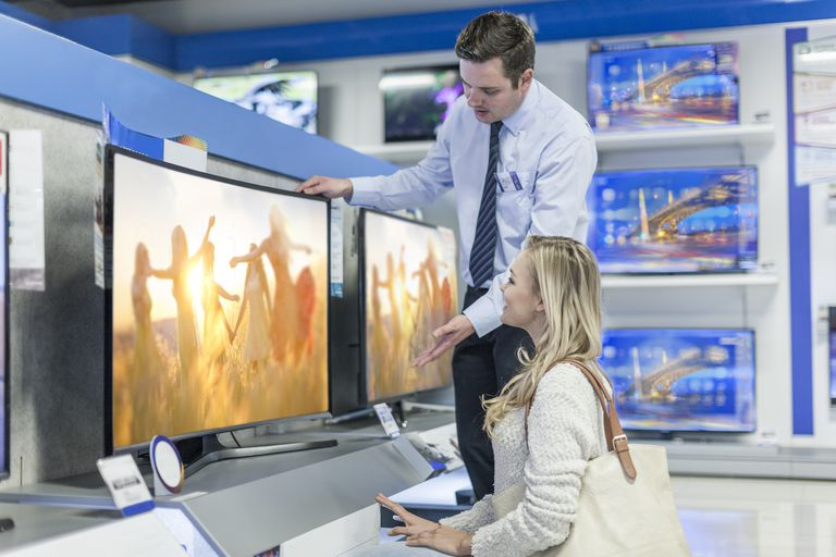 Shop assistant showing flatscreen TV to customer
