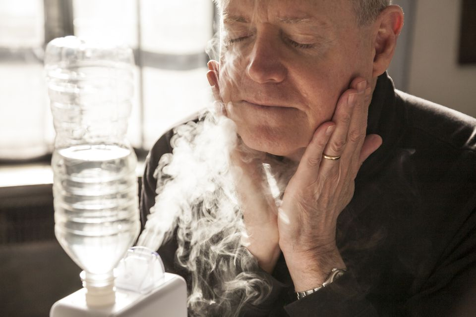 Mature man hydrates with home humidifier.