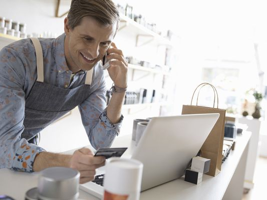 Smiling male shop owner talking on cell phone and working at laptop in home fragrances shop