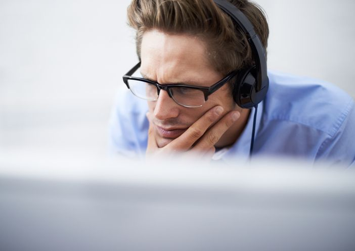 A handsome young businessman wearing a headset while concentrating on his computer screen