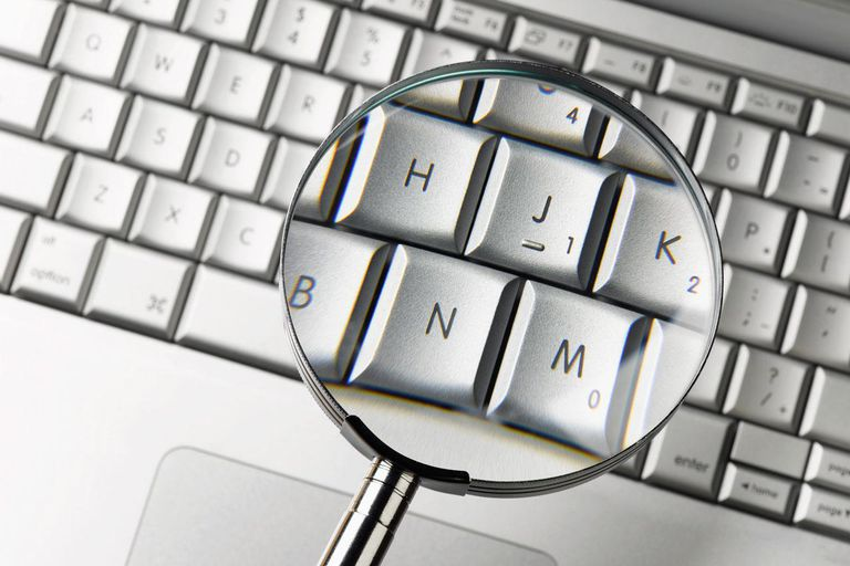Magnifying glass over laptop keyboard