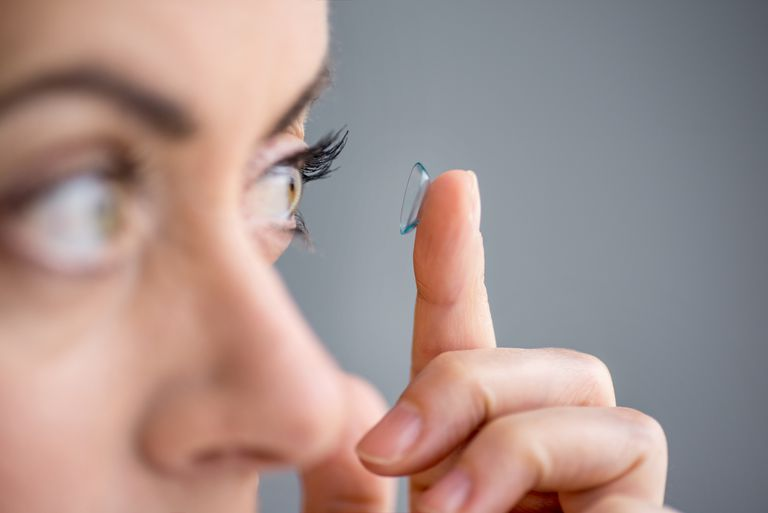 Woman putting contact lens in her eye