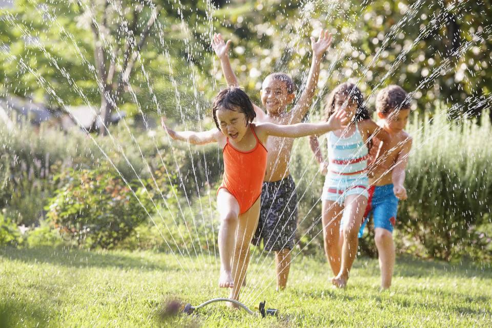 Children running through water sprinkler