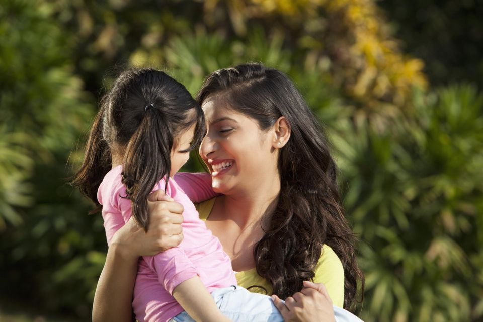 Mother holding daughter (6-7) in park