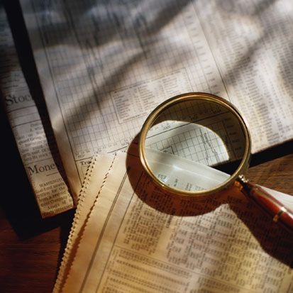 Magnifying glass on top of newspaper stock reports