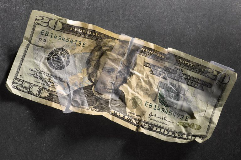 Torn twenty dollar bill, repaired with tape