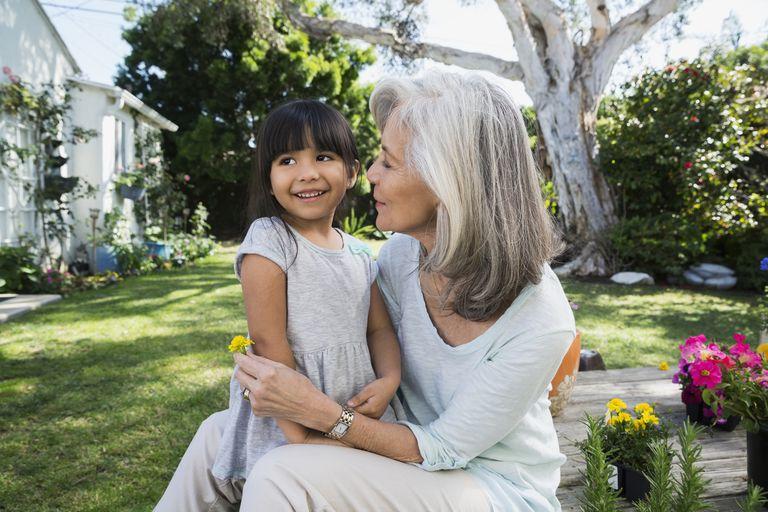 Granddaughter and grandmother hugging in backyard garden