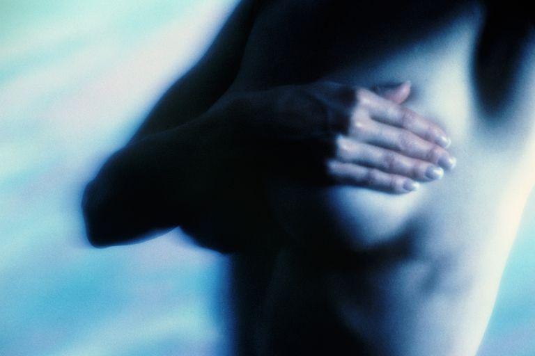 Naked young woman examining breast, mid-section (focus on hand)