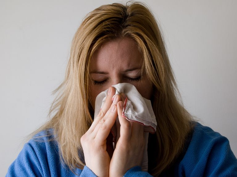 a woman sneezing, possibly due to allergies