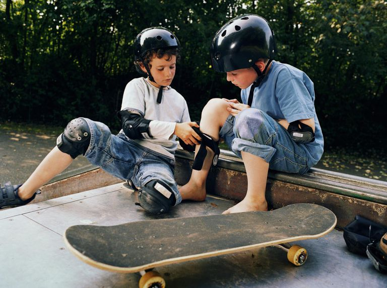 Two boys (7-9) on skateboard ramp, one adjusting knee pad of other