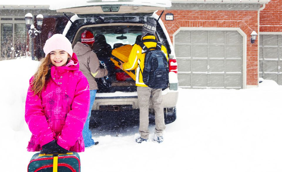 Young girl standing outside a packed car in the snow.