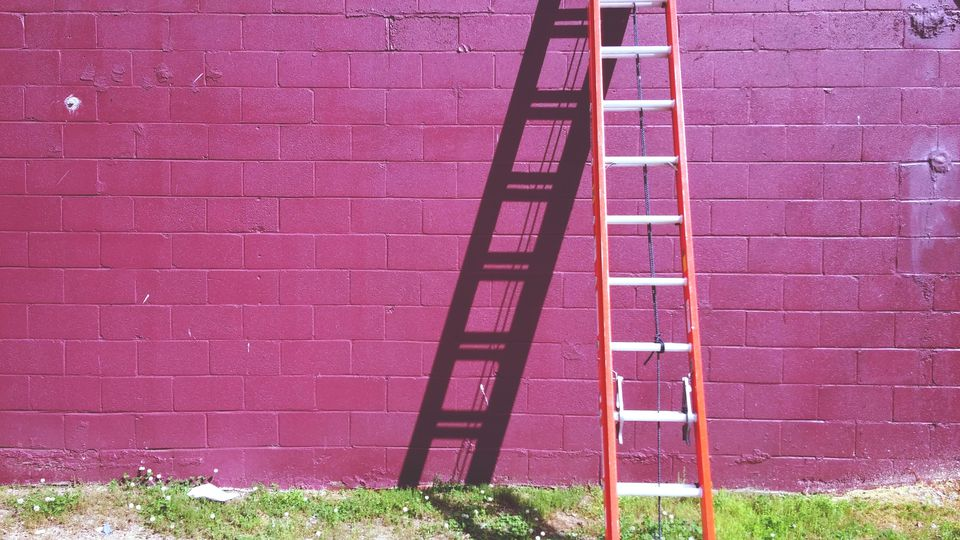 Ladder Leaning Against Pink Brick Wall