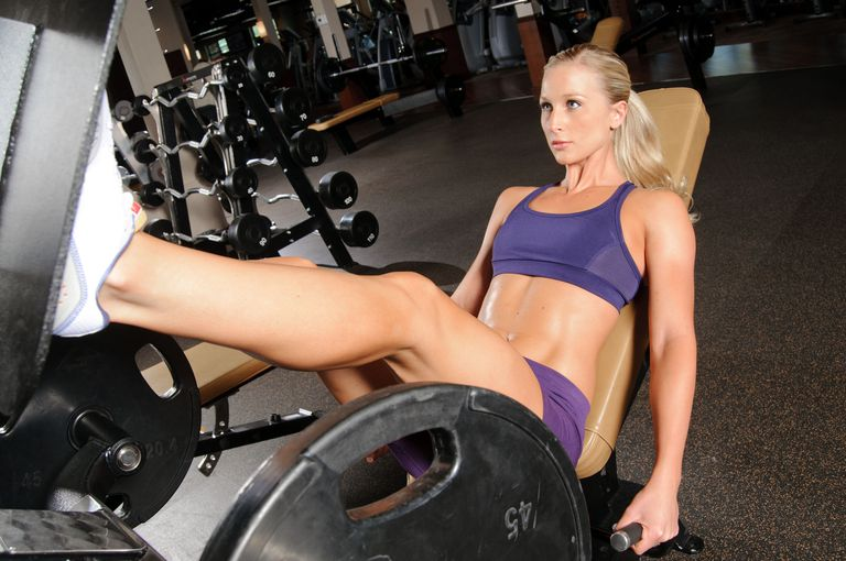 Fit woman using leg press