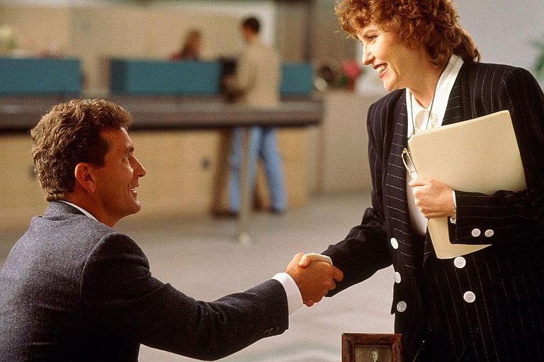 Businessman shaking hands with female
