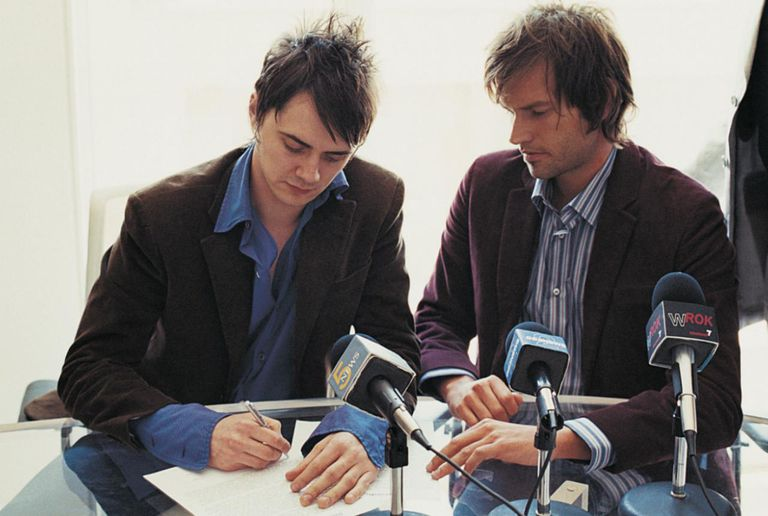 Pop Musicians Signing a Contract in a Conference Room Attended by Their Manager