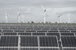 Wind turbines stand behind a solar power park