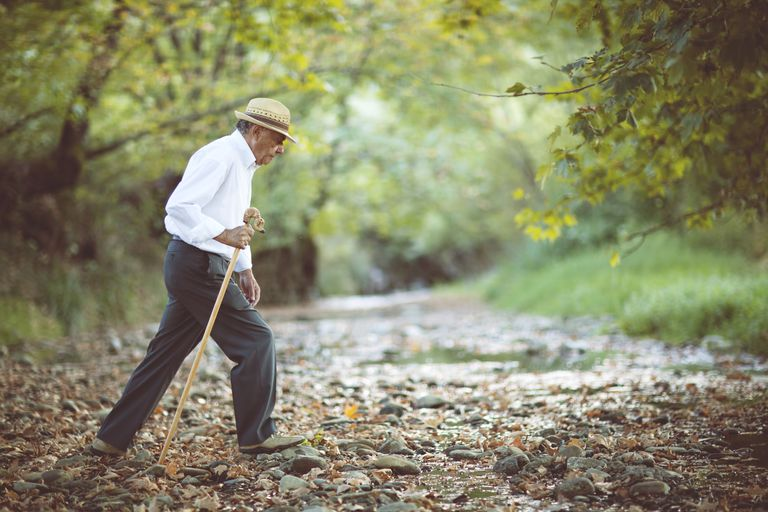 Old man walking in a creek bed
