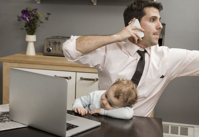 Father working multi-tasking with son