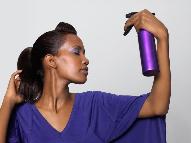 black woman spraying hair with natural hair spritz