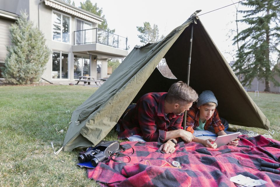 Father and son using digital tablet in backyard tent