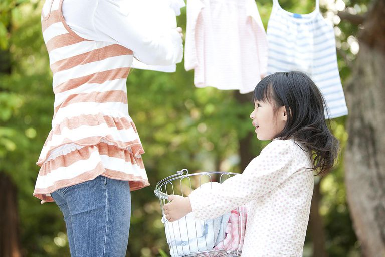 Girl helping mother drying laundry, smiling